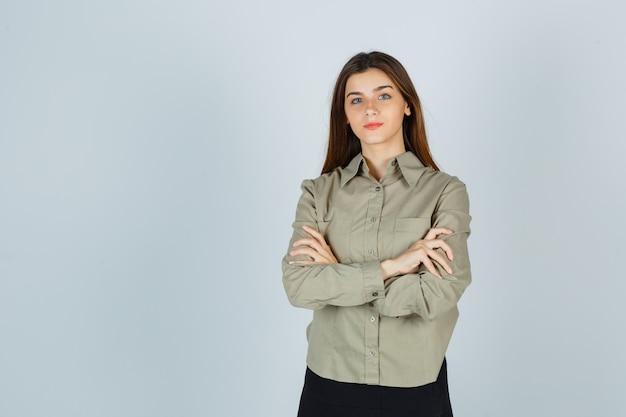 Симпатичная молодая женщина, стоящая со скрещенными руками в рубашке, юбке и гордо выглядящая. передний план.
