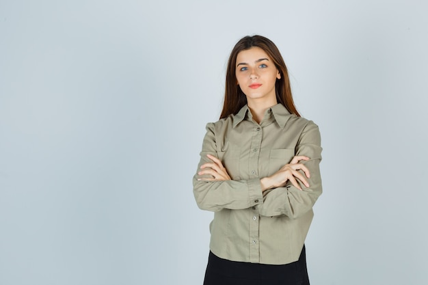 Cute young female standing with crossed arms in shirt, skirt and looking proud. front view.