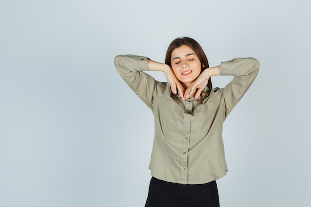 Cute young female stretching elbows while shutting eyes in shirt, skirt and looking delighted. front view.