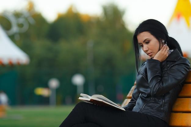 Милая молодая студентка в кожаной черной куртке читает книгу, сидя на скамейке в парке в теплый осенний день