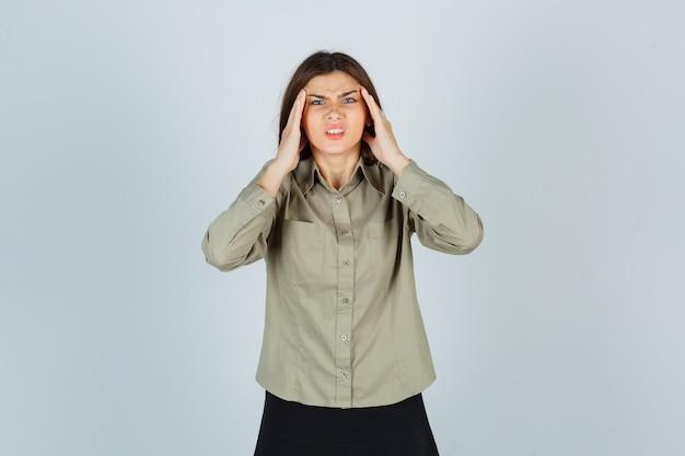 Carina giovane donna che soffre di forte mal di testa in camicia, gonna e sembra irritata. vista frontale.