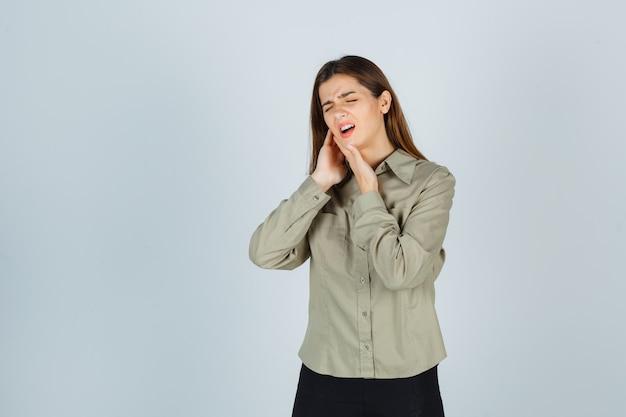 Carina giovane donna che soffre di mal di denti in camicia, gonna e sembra dolorosa, vista frontale.