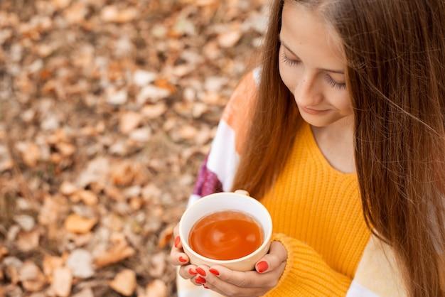 귀여운 젊은 여성 여행자는 숲에서 쉬고 흰색 컵에서 뜨거운 차를 마십니다. 가을 시간, 여행, 자연 위를 걷는 것, 복사 공간.