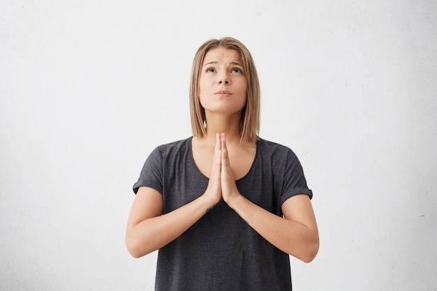 Cute young female wearing casual t-shirt keeping palms pressed together having sorrowful expression looking up begging for good luck in future isolated.