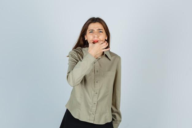 셔츠, 치마에 손가락으로 휘파람을 불고 흥분하는 귀여운 젊은 여성. 전면보기. 무료 사진