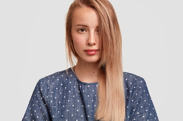 Cute young female with long hair combed on one side, looks seriously, shows her healthy perfect skin, dressed in polka dot blouse, poses against white wall. people, beauty, lifestyle concept