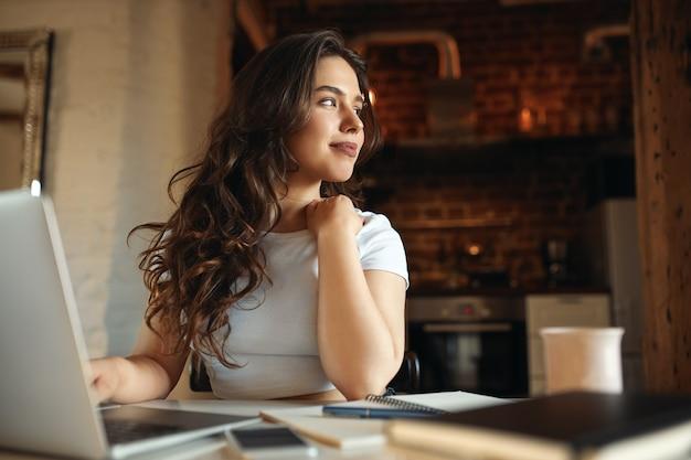 꿈꾸는듯한 표정을 가진 먼 작업을 위해 휴대용 컴퓨터를 사용하여 화창한 날을 즐기는 긴 물결 모양의 머리를 가진 귀여운 젊은 여성. 집에서 노트북에 온라인 공부 매력적인 학생 소녀. 선택적 초점