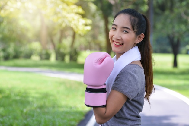 Cute young fitness girl in pink boxing gloves in park, smiling with camera