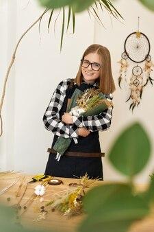 꽃이 게에서 마른 꽃의 아름 다운 가을 꽃다발을 들고 귀여운 젊은 꽃집 여자