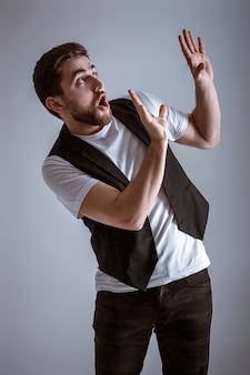 Симпатичный молодой испуганный мужчина с бородой в белой рубашке и черном жилете на сером фоне