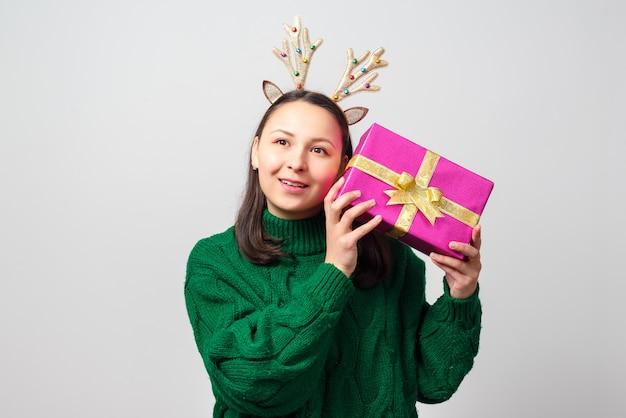 크리스마스 사슴으로 옷을 입고 귀여운 젊은 재미있는 여자는 선물로 기뻐합니다
