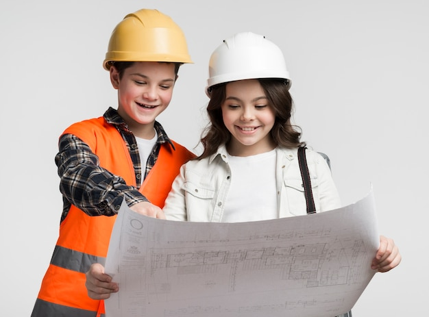 귀여운 어린 소녀와 소년 건설 계획을 읽고