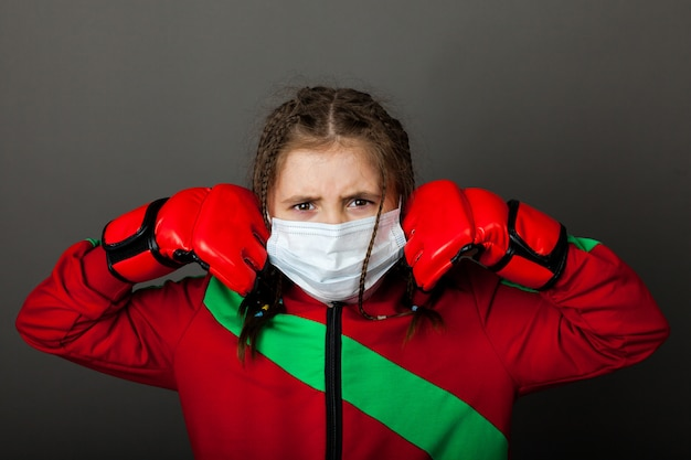 Cute young girl boxer in a medical mask and boxing gloves is standing in a boxing rack.