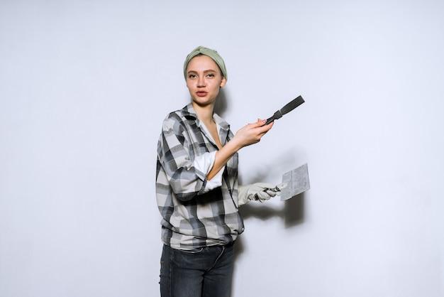 Симпатичная молодая девушка-строитель делает ремонт, держа в руках шпатель и кисть