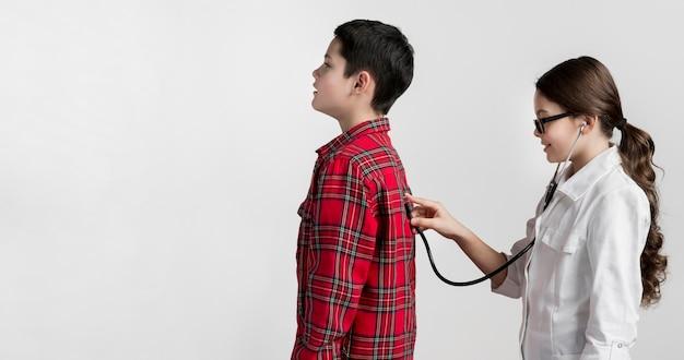 Милая маленькая девочка проверяя здоровье мальчиков