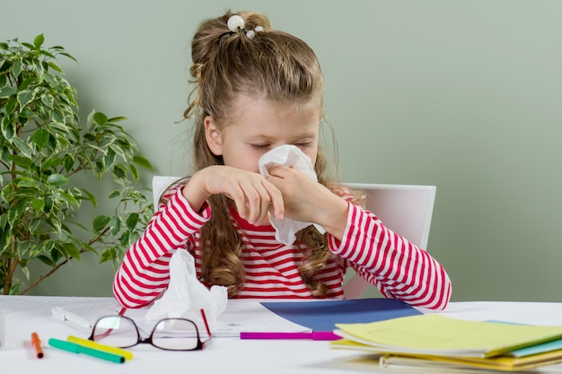 Cute young girl child in glasses sneezing in tissue