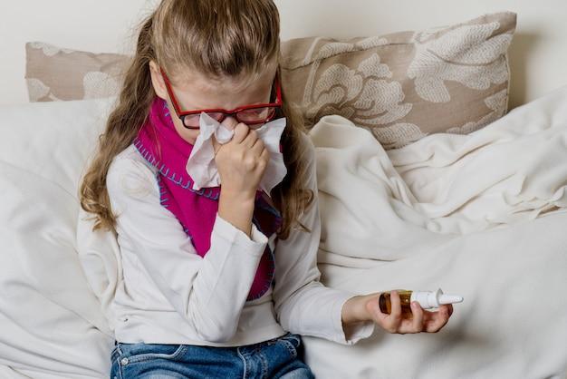 Милая маленькая девочка ребенок в очках, чихание в ткани дует