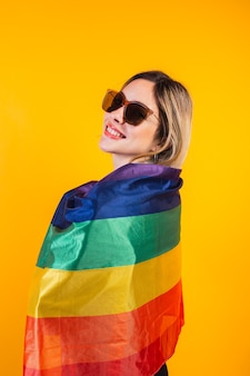Cute young girl drapes herself with large rainbow flag on yellow background.