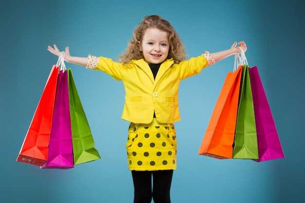 Cute young girl dressed all in yellow hold different bags