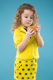 Cute young girl dressed all in yellow with burger
