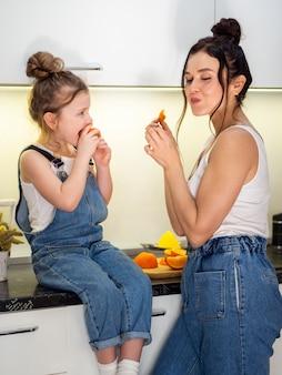 Милая молодая девушка ест апельсин с матерью