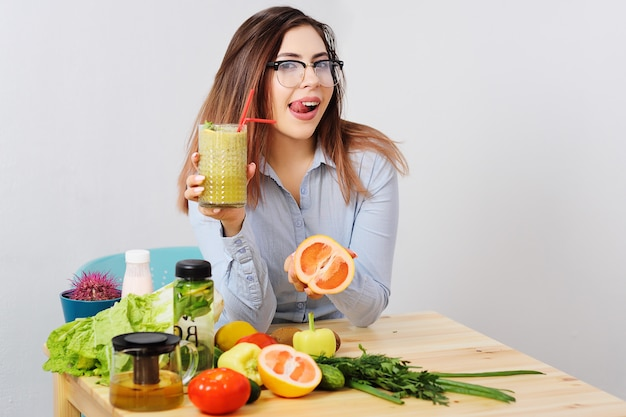 Cute young girl in glasses with a glass of smoothies in hands.
