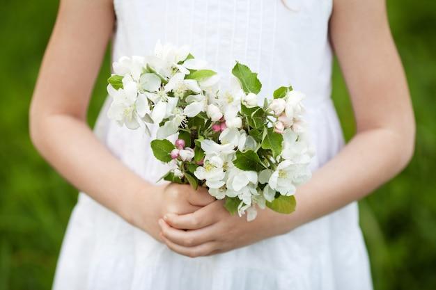 リンゴの花の花束を持っているかわいい少女。咲くリンゴの木と庭の白いドレスの美しい少女。