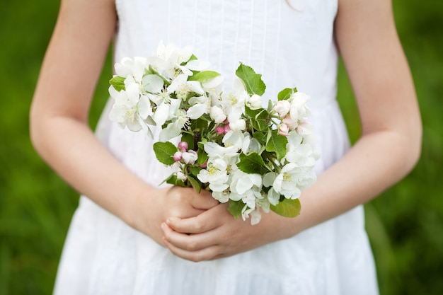 Cute young girl  holding a bouquet of apple flowers. beautiful  girl in white dress in the garden with blosoming  apple trees.