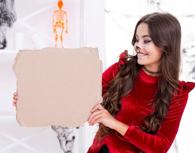 Симпатичная молодая девушка держит картонный знак