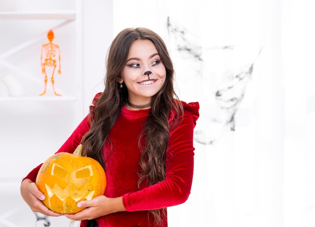 Cute young girl holding carved pumpkin
