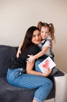 Симпатичная молодая девушка обнимает ее прекрасную мать