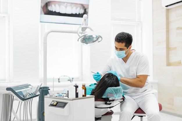 귀여운 소녀는 치과 의사에 의해 검사되고있다
