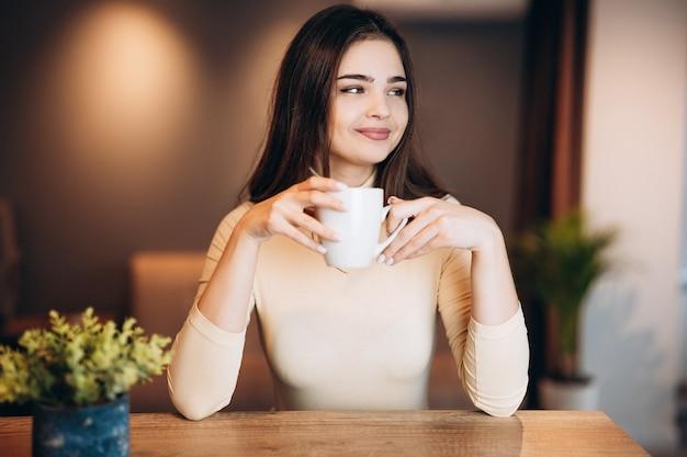 귀여운 어린 소녀는 작업 / 공부하는 동안 집에서 커피를 마시고있다