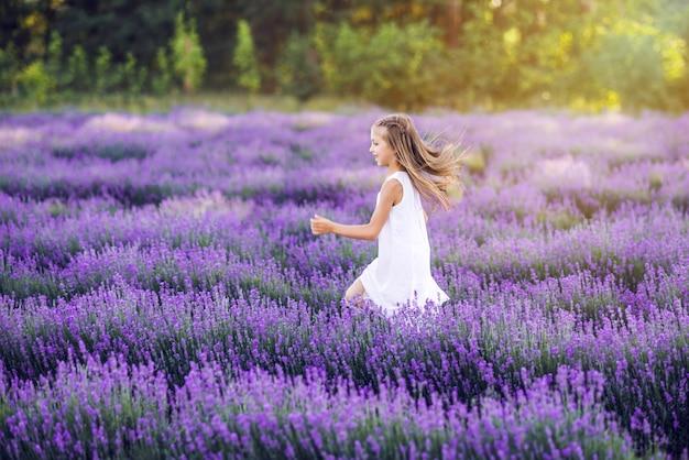 Милая молодая девушка бегает в лавандовом поле. на ней белый сарафан.