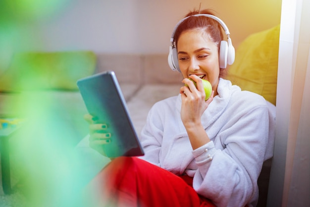 Cute young girl listening to the music and looking at the tablet. eating green apple and relaxing.