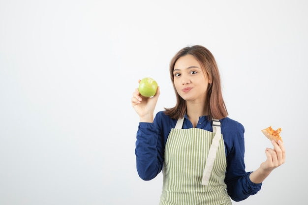 Un modello di ragazza carina in grembiule che tiene una mela e un pezzo di pizza.