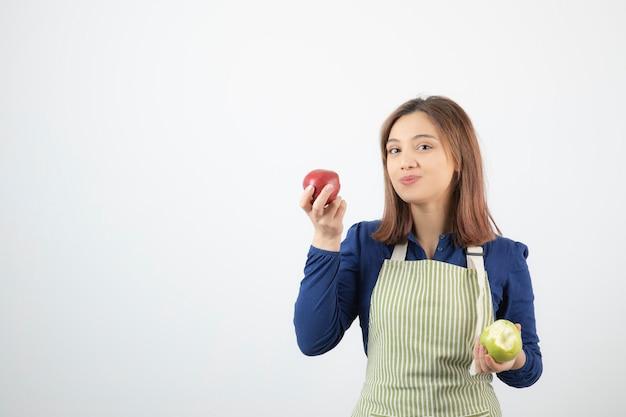 Un modello di ragazza carina in grembiule che tiene le mele.