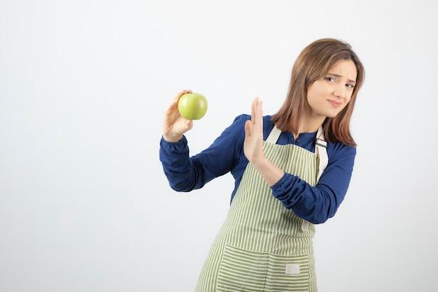 Un modello di ragazza carina in grembiule che rifiuta da una mela fresca verde.