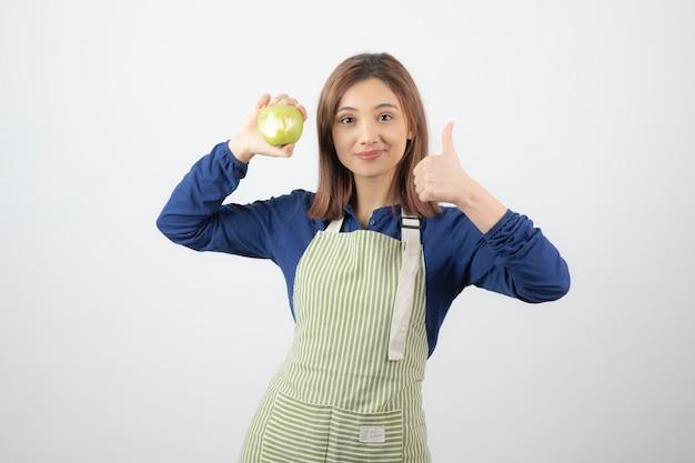Un modello di ragazza carina in grembiule con una mela fresca verde che mostra un pollice in su.