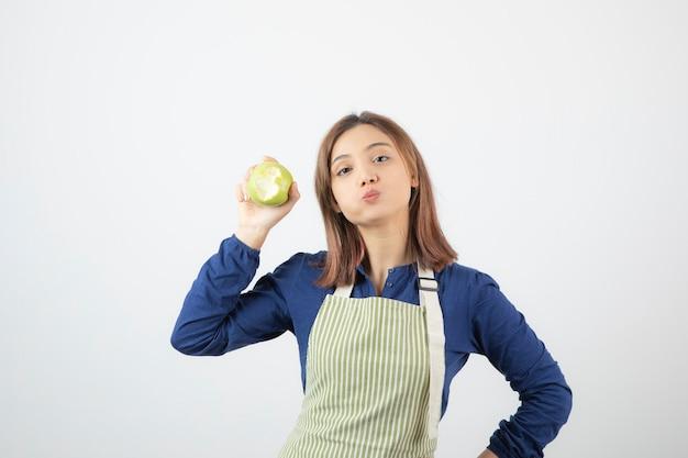 Un modello di ragazza carina in grembiule con una mela fresca verde.