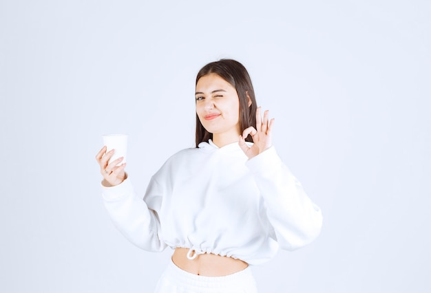 Cute young girl model with a plastic cup showing ok gesture.