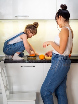 Cute young girl and mother together in the kitchen