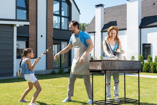 Cute young girl playing with her father while helping them to prepare barbeque
