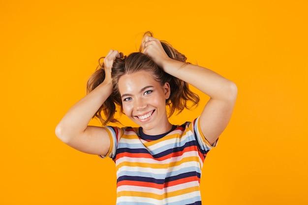Милая молодая девушка позирует на желтой стене, держа в руках волосы.