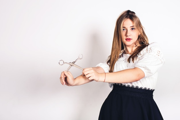 Cute young girl posing with scissors in her hands.