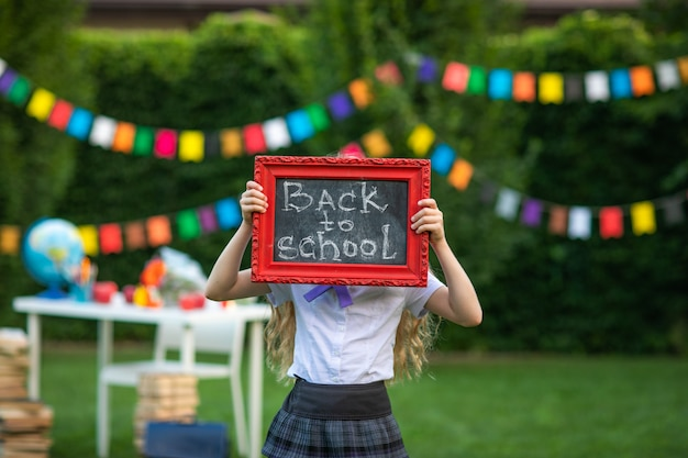 Cute young girl posing with small school board against flags background.