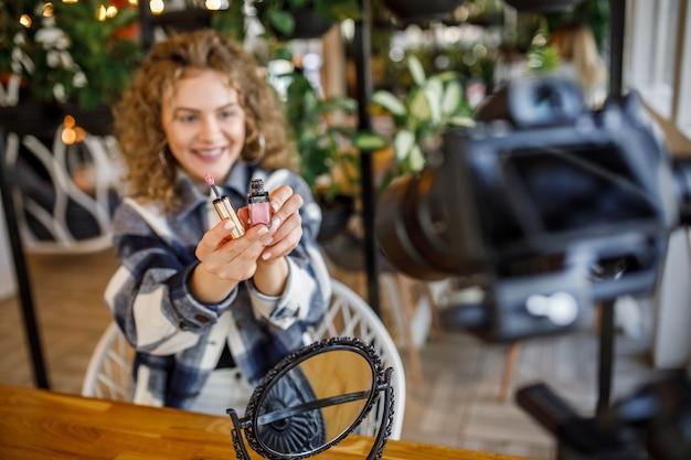 自宅のテーブルに座って化粧をしながら、新しい化粧品の口紅製品についての彼女のビデオブログエピソードを記録しているかわいい若い女の子