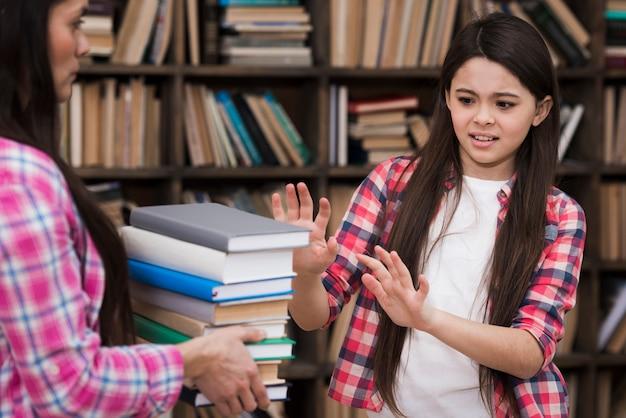 Симпатичная молодая девушка отказывается брать кучу книг