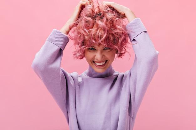 귀여운 어린 소녀가 외진 벽에 곱슬곱슬한 분홍색 머리를 헝클어뜨립니다.