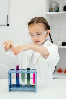Милая молодая девушка-ученый с пробирками делает эксперименты